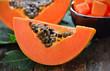 canvas print picture - papaya slice on wood