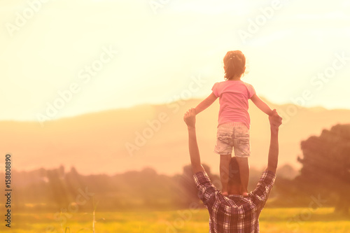 Fotomural Silhouettes of father and daughter playing together in the cornfield at sunset