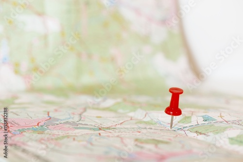 Fototapety, obrazy: Single red pushpin marking a location on an open map
