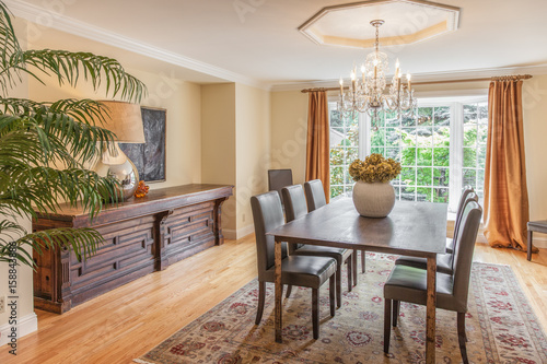 Fotografía  Elegant dining room with wood table and chandelier