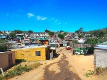 Street Of Colorful Informal Settlements (Slum), Huts Made Of Metal In The Township Or Cape Flats Of Stellenbosch, Cape Town, South Africa With Blue Sky And Clouds Background