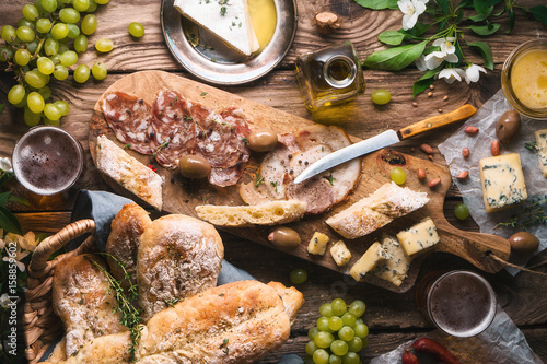 Homemade bread, cheese, olives, grapes, flowers on old boards Canvas-taulu