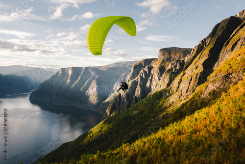 Fotobehang Luchtsport Paraglider silhouette flying over Aurlandfjord, Norway