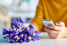 Closeup Portrait Of Unrecognizable Young Man Using Smartphone While Waiting For Date With Bouquet Of Flowers