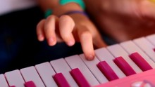 Macro Little Finger Presses Keys On Pink Piano One By One