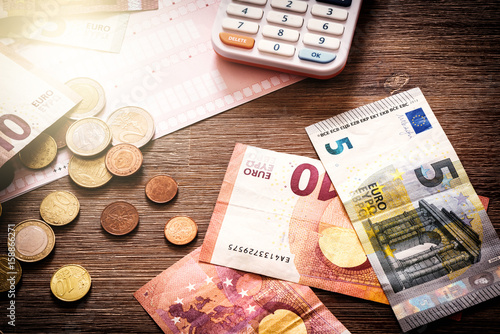 Fotografía  Euro banknotes and coins with bills to pay