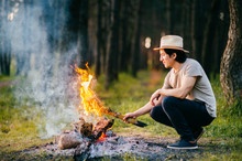 Native American Redskin Indian Peruvian Indigenous Man In Straw Hat Sitting In Forest Outdoor In Summer Above Bonfire With Smoke And Torch At Hand. Shaman Rite. Spiritual Ceremony. Young Sorcerer.