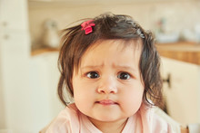 Portrait Of Cute Baby Girl Pulling A Face