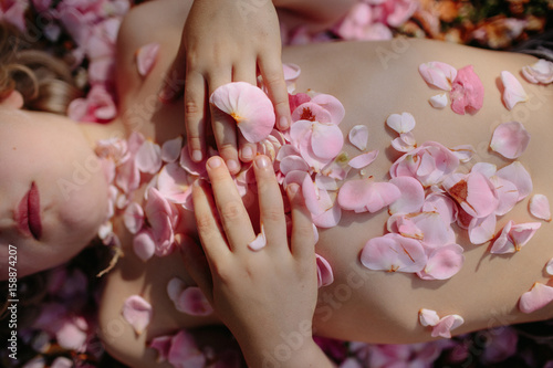 Person covered in flower petals, mid section, overhead view