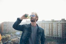 Young Man Drinking From Beer Bottle At Roof Party