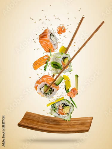Poster Sushi bar Flying sushi pieces served on plate, separated on colored background