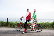 1950's Vintage Style Couple Looking Out From Tandem Bicycle At Coast