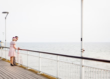1950's Vintage Style Couple Looking Out From Pier