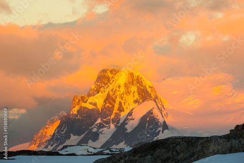 Glowing red mountains at sunset in Antarctica плакат