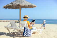 Back View Of Father And Daughter Using Tablet Pc On The Beach. Holiday Relaxation Vacation Photography On Sunny Blur Sky Seacoast Shore Outdoors Background