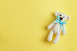 canvas print picture - Bear toy with turquoise bow-knot over yellow background