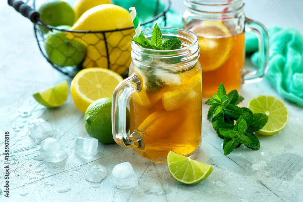 Fototapeta Iced tea, summer cold drink  with lemon and mint, limes and ice cubes, refreshment