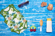 Baby Child summer stuff to the beach on a blue wooden background. Top view with copy space for text.