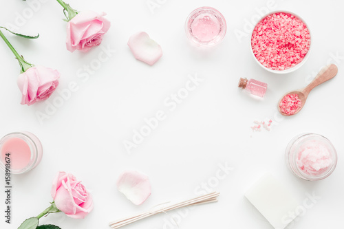 Fotomural  homemade spa with rose cosmetic set, cream, salt and oil on white background top