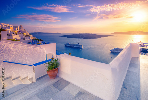 Fotobehang Santorini Amazing evening view of Fira, caldera, volcano of Santorini, Greece with cruise ships at sunset. Cloudy dramatic sky.