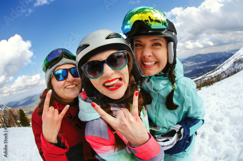 Cheerful snowboarder posing on top of a mountain