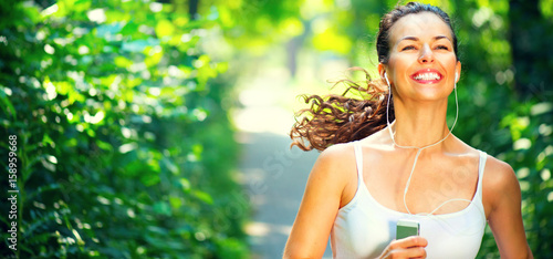 In de dag Jogging Running sporty girl. Beauty young woman with earphones jogging in the park