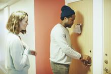 Woman Looking At Male Friend Opening Door Lock In College Dorm