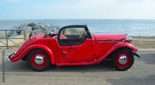 Photo  Classic  Red  Singer  Car  parked on seafront promenade with sea in background