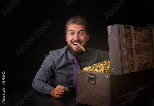 Photo Schatztruhe mit Geldstücken erfreut schönen Mann mit Zigarre