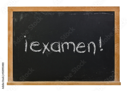 Foto  Exam written in Spanish in white chalk on a black chalkboard isolated on white