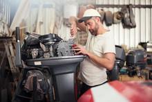 Man Repairing Outboard Motor In Boat Repair Workshop