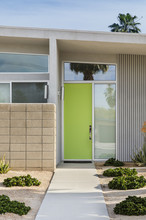 Close Up Of A Lime Green Front Door With Drought Resistance Plants Lining The Entrance