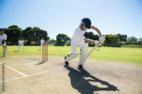 Carta da parati Young man playing cricket at field against clear sky