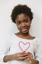 Girl Holding A Heart Shaped Pipe Cleaner Against White Background