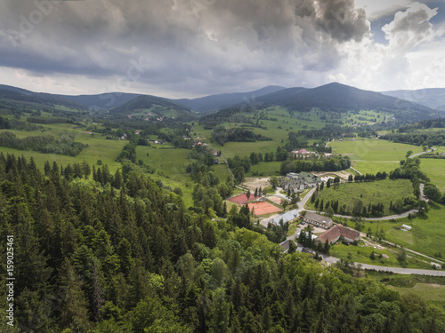 Fotobehang Rijstvelden Aerial view of the summer time in mountains near Stronie Slaskie town in Poland. Pine tree forest and clouds over blue sky. View from above.