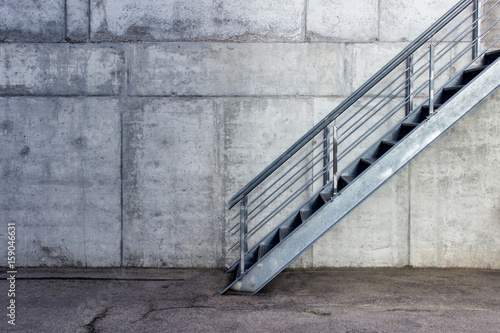 Staande foto Industrial geb. Metallic staircase on the background of gray cement wall - urban minimalist exterior.