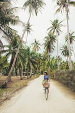 Woman Riding A Bike On A Tropical Island