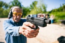 Shooting Senior Male Aims Handgun At Target