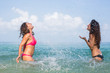 Two Women in the Ocean Splashing Water at Each Other