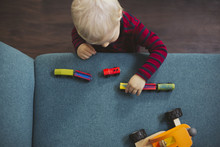 Blond Boy Playing With Toy Cars