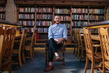 Portrait Of Young Man In Library On College Campus