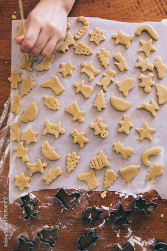 Girls hand adding detail to Christmas biscuits before baking