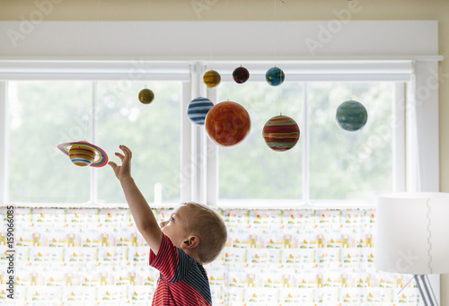 Child Playing with Solar System Mobile