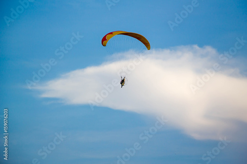Poster Luchtsport man flying with paramotor engine glider parachute on beautiful blue sky