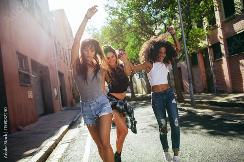 plakat Beautiful women having fun on city street