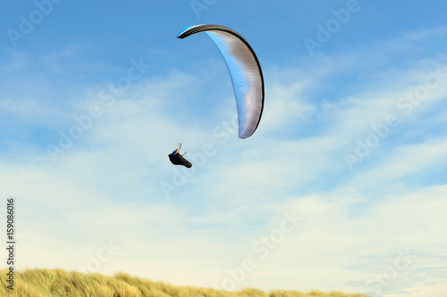 Foto op Canvas Luchtsport Para gliding above the dunes near the coastline