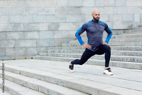 Photo Sportive man exercising between staircases in the city