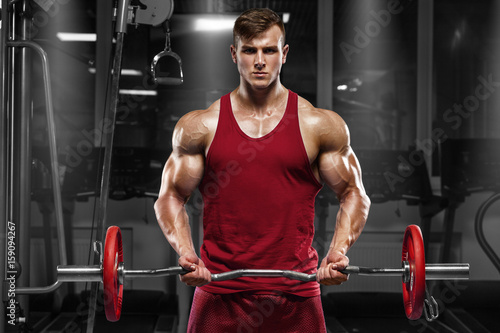 Foto op Plexiglas Fitness Muscular man working out in gym doing exercises with barbell, strong male