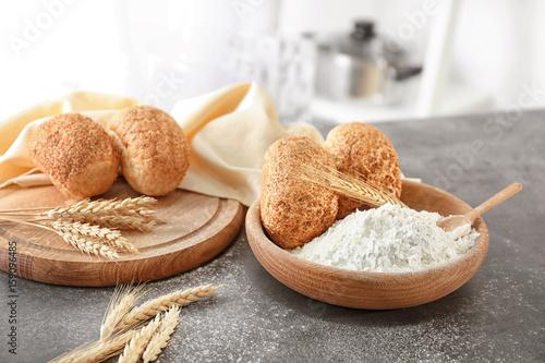 In de dag Bakkerij Bowl of wheat flour and fresh bread on blurred background