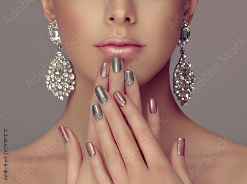 Montage in der Fensternische Maniküre Beautiful model girl with pink and gray silver metallic manicure on nails . Fashion makeup and cosmetics . Big silver diamond shine earrings jewelry .